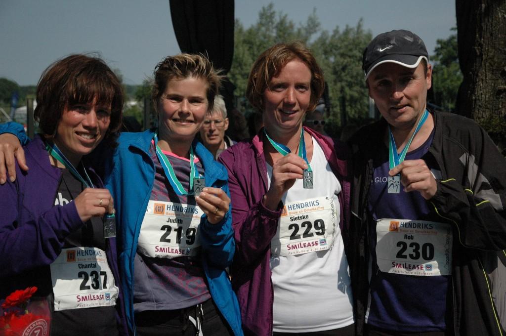 Een beetje moe maar voldaan tonen Chantal, Judith, Sietske en Rob hun verdiende marathonmedaille.